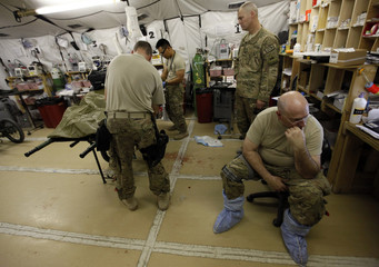 U.S. Army Colonel Somberg MD. and Chaplain Captain Wright pause as U.S. soldier waits to be transferred to higher level military hospital at FOB Shank in Logar province