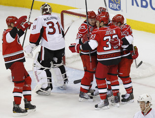 Carolina Hurricanes players celebrate after scoring a goal against Ottawa Senators during their NHL hockey game in Raleigh