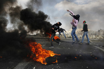 Palestinians protesters throw stones towards Israeli security officers during clashes on Land Day in East Jerusalem