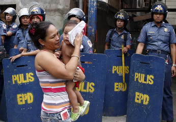 A woman carries her baby past policemen standing guard during a demolition of shanties at a squatter colony, to pave way for private modern housing projects in Mandaluyong