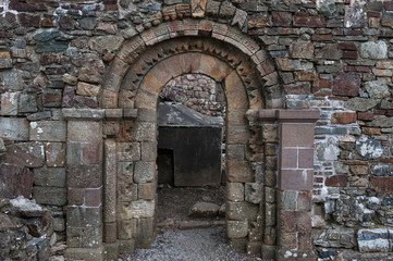 Stone wall archway door entrance of old celtic church ruins in Ireland
