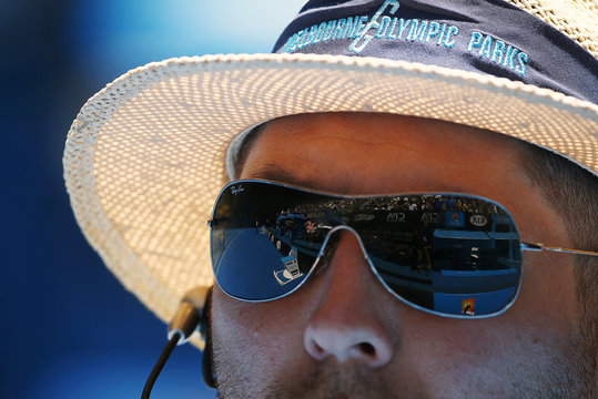 Rod Laver Arena is refllected in a security guard's sunglasses during the Australian Open 2015 tennis tournament in Melbourne