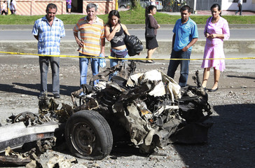 People look at the remains of a car bomb in Popayan