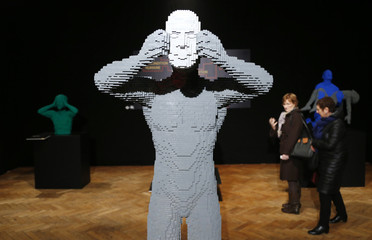 """Visitors walk behind the art work titled """"Mask"""" during """"The Art of the Brick"""" exhibition in Brussels"""
