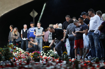 A man lays flowers in the tunnel where revellers died during a stampede at the Love Parade techno festival in Duisburg