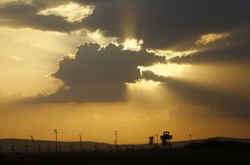 A Turkish border watch tower is silhouetted against the sunset at the Turkish-Syrian border near the southeastern town of Suruc in Sanliurfa province