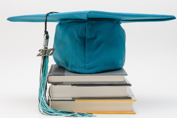 Graduation cap, tassel and books for students
