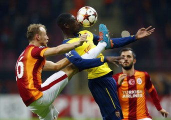 Galatasaray's Kaya challenges Arsenal's Sanogo during their Champions League Group D soccer match at Ali Sami Yen Spor Kompleksi in Istanbul