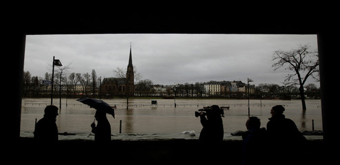 """People are silhouetted as they look at a flooded street between river Main and Frankfurt's historical city """"Roemerberg\"""