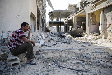 A Palestinian man smokes as he sits among the ruins of buildings in Khuzaa