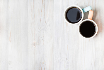 Two cups of coffee on white wooden table. Top view, flat lay.