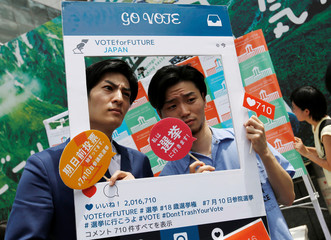 Saiki, head of a conservative non-profit organisation, and Okuda, founding member of SEALDs, pose with an Instagram frame calling on youths to vote in the July 10 upper house election, in Shibuya district in Tokyo