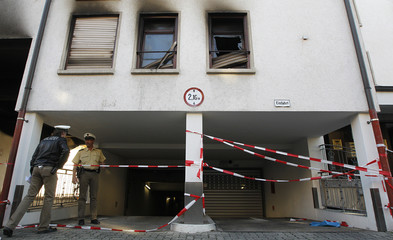 Police officers officer stands guard in front of a burnt apartment building in Loerrach