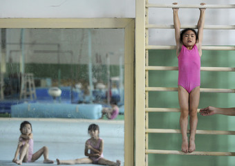 A girl stretches on wooden bars as her classmates are reflected in the mirror at a local gymnastic school in Nanjing