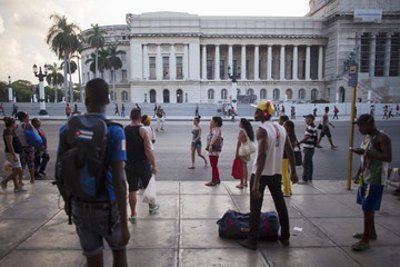 People wait for a public bus in front of Cuba's Capitol, or El Capitolio as it is called by Cubans in downtown Havana