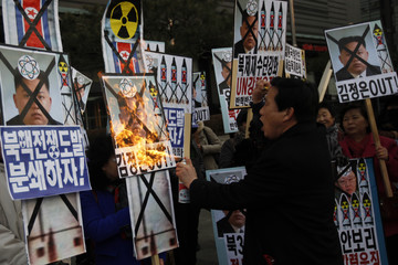 An activist from an anti-North Korea civic group burns a portrait of North's leader Kim Jong-un during a rally against North Korea's nuclear test near the U.S. embassy in central Seoul