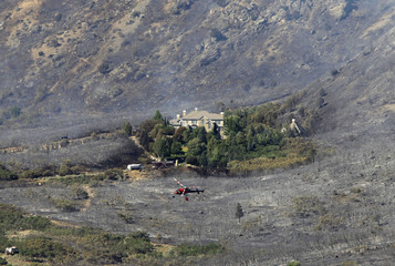 A house is surrounded by a burnt landscape, as a helicopter flies above after dropping water on the Quail Fire in Alpine
