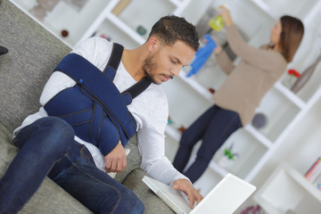 Man with arm in sling using laptop computer