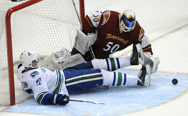 Thrashers goaltender Chris Mason blocks a shot from Vancouver Canucks Daniel Sedin who slides into the goal after being pushed in the first period of their NHL hockey game in Atlanta