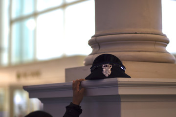 """A police officer rests her hat atop a column while using her phone at the 2017 """"Congress of Tomorrow"""" Joint Republican Issues Conference in Philadelphia"""