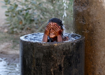 A girl bathes to cool off herself with water that is leaking from a broken pipe valve on a hot summer day on outskirts of Ahmedabad