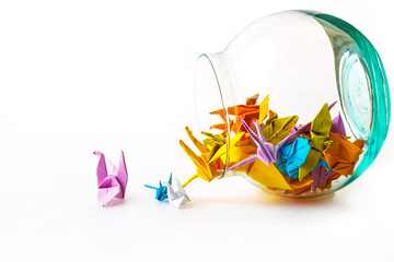 Think out of the box concept, a lot of paper birds in a grass jar and some paper birds on the table