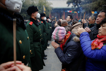 People pray and hold incense sticks in front of paramilitary policemen providing security as people gather at Yonghegong Lama Temple on the first day of the Lunar New Year of the Rooster in Beijing