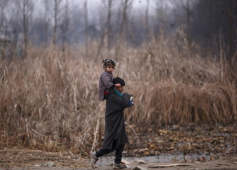 A boy carries a girl on his shoulders, on a cold winter morning in Srinagar