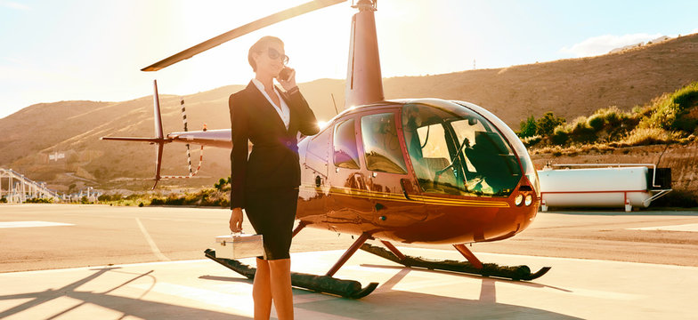 Business woman talking by phone near the helicopter