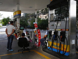 Petrol pump attendants watch the game between Brazil and Chile on a small television set during a 2014 World Cup round of 16 game, in Sao Paulo