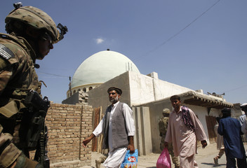 Residents walk past  U.S. soldiers from Task Force Bronco, 3rd Squadron, 4th Cavalry on a patrol in Rodat district in Jalalabad
