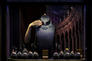 An exhibitor arranges jewellery behind a window display at the Hong Kong International Jewellery Show