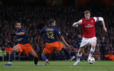 Arsenal's Per Mertesacker goes past Montpellier's Daniel Congre and Abdel El Kaoutari during their Champions League Group B soccer match in London