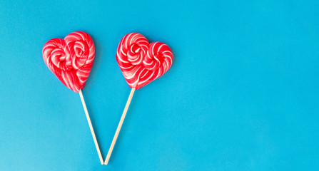 Valentines Day heart shaped lollipops on a vibrant blue background with copy space