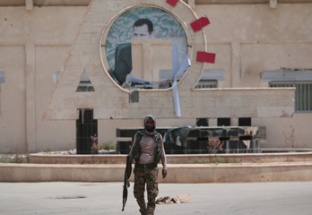 A Kurdish fighter from the People's Protection Units (YPG) carries his weapon as he walks at the faculty of economics where a defaced picture of Syrian President Bashar al-Assad is seen in the background, in the Ghwairan neighborhood of Hasaka