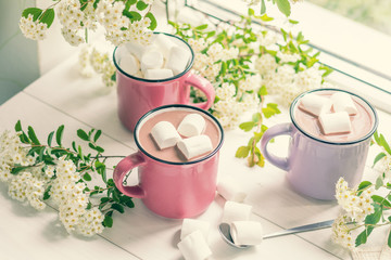 Hot cocoa with marshmallows in pink cups and fresh spring white flowers on the windowsill. Cozy home concept. Shallow depth of field.
