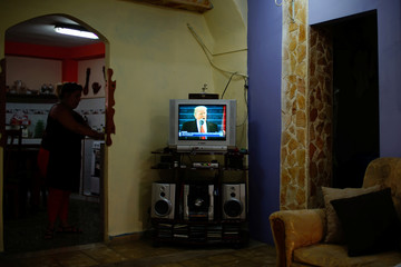 Mariza Betancourt, who runs a small hostal in downtown Havana, works as she listens to the inauguration ceremonies to swear in U.S. President Donald Trump, seen on TV in Havana, Cuba