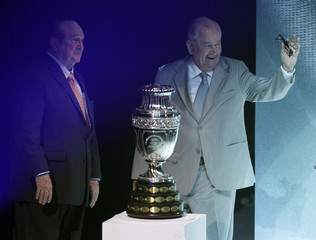 President of the AFA Grondona waves after receiving the Copa America trophy from the President of the South American Soccer Confederation Leoz during draw ceremony for 2011 Copa America soccer tournament