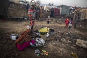 A woman, whose family moved to Islamabad from Sargodha in Punjab Province to look for jobs, washes dishes in Islamabad