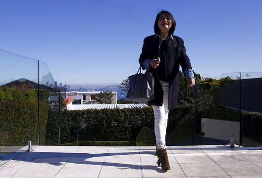The Sydney Opera House and Harbour Bridge can be seen behind Bao Fang, a potential buyer from Shanghai, as she inspects a property for sale in the Sydney suburb of Vaucluse, Australia