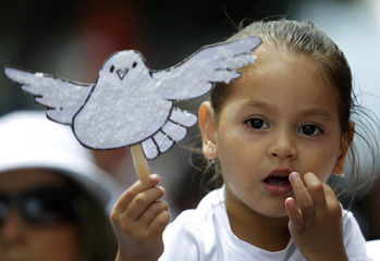 "A student holds up a white paper dove during a march called ""The right to live in peace"" in San Jose"