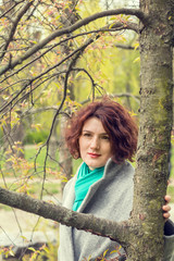 Pretty young red head woman close to the tree in spring park. Spring trees background.