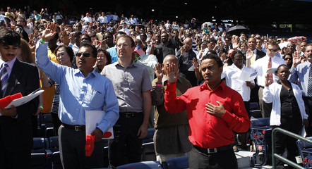 The Oath of Allegiance is administered to 1,094 new American citizens during a special naturalization swearing-in ceremony at Turner Field in Atlanta