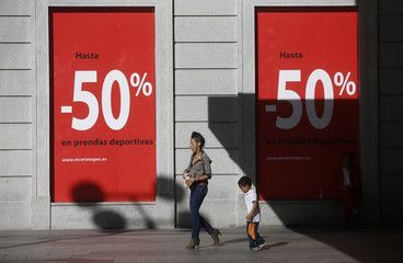 People walk past a banner advertising sales in a shopping mall in Madrid