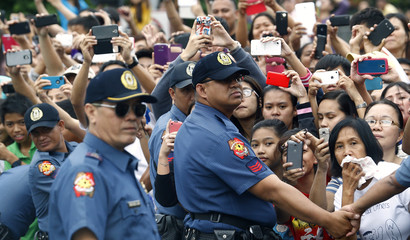 People hold mobile devices as they wait for Pope Francis' convoy alongside a street in Manila