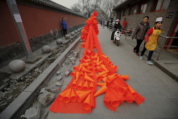 Chinese artist Kong Ning walks through a historical part of Beijing in her costume made of hundreds of orange plastic blowing horns during her art performance raising awareness of the hazardous smog on a very polluted day