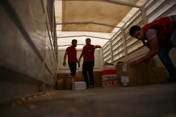 Men unload aid boxes from a Red Crescent aid convoy carrying urgent medical supplies in the rebel held besieged town of Douma