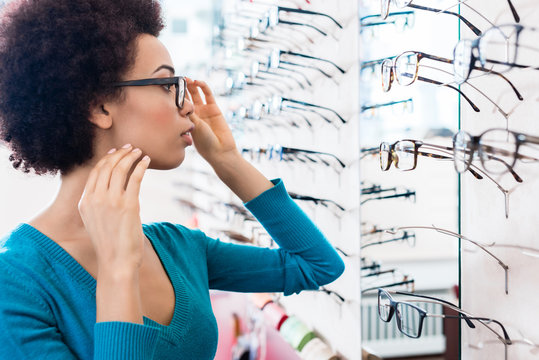 Black woman trying on glasses in optician store