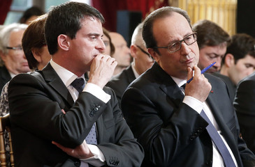 French President Francois Hollande listens to French Prime Minister Manuel Valls, during the Environmental Conference at the Elysee Palace in Paris