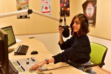 Portrait of happy young female radio host broadcasting in studio